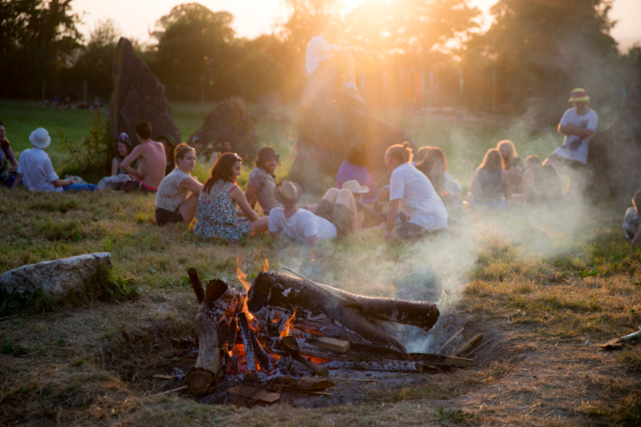 People relax on lush grass as the sun sets behind a row of trees. A campfires smoulders in the foreground.