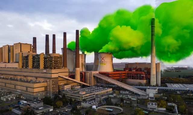 Photo illustration shows plumes of green steam coming from a power station cooling tower
