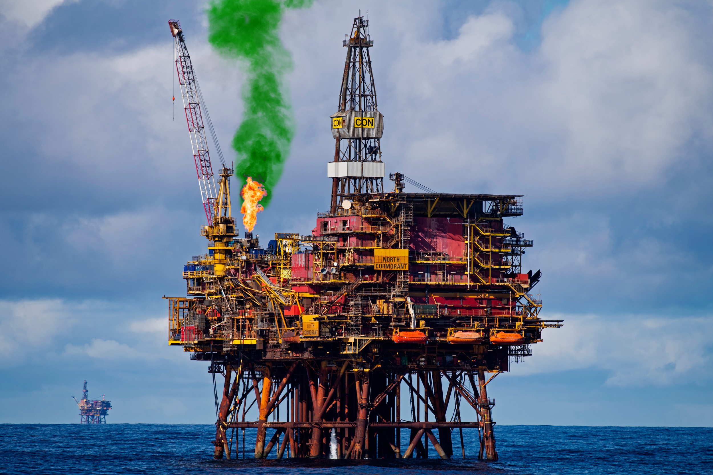 Photo illustration shows an oil rig with a plume of green smoke coming from the flaring tower.