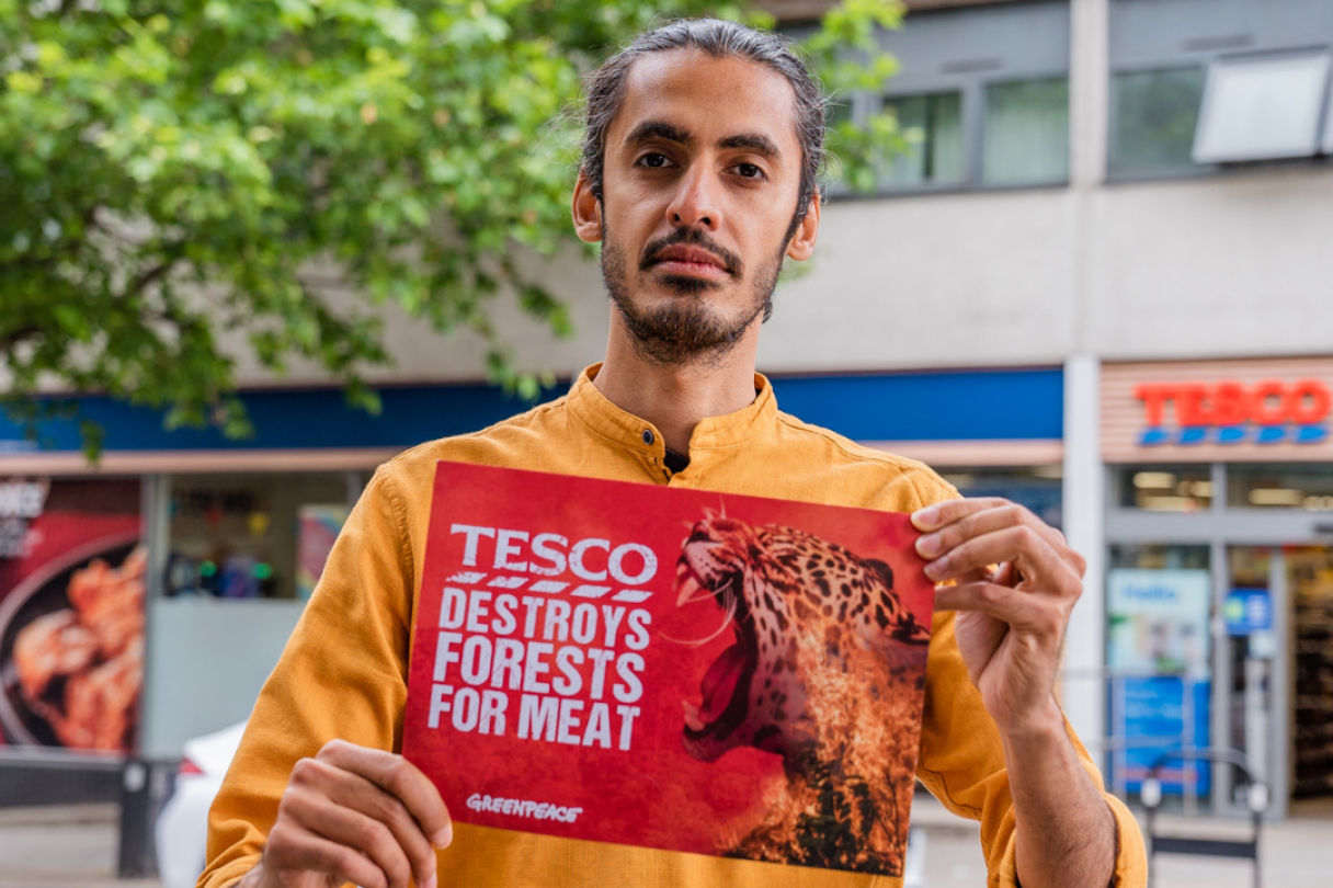 """Activist holds up a sign reading """"Tesco destroys forests for meat"""""""