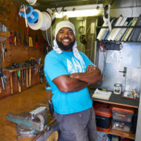 Apisalome, a member of the Rainbow Warrior ship crew stands in front of a well-equipped tool bench, smiling into the camera with arms folded.