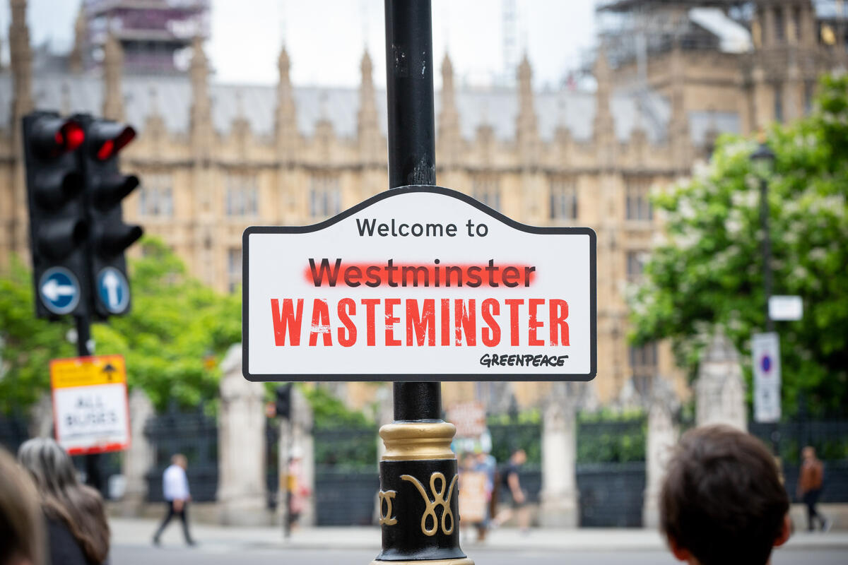 A sign reading 'Welcome to Westminster' attached to a lamp post with the houses of parliament in the background. The word 'Westminster' has been crossed out and replaced with 'Wasteminster'.