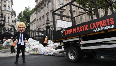A tipper truck with 'Stop plastic exports' stencilled on the side drops bags of plastic waste outside the gates of Downing Street. An activist wearing a caricatured Boris Johnson mask looks on.