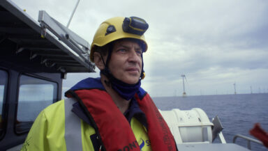 Alan (hard hat, life jacket, hi-vis) looks out on an offshore windfarm from the deck of a work boat