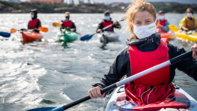 An activist (red buoyancy aid, long hair tied back, cloth facemask) smiles into the camera. A row of other kayakers is visible in the background.