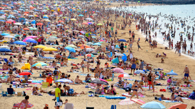 A crowded beach with lots of colourful umbrellas