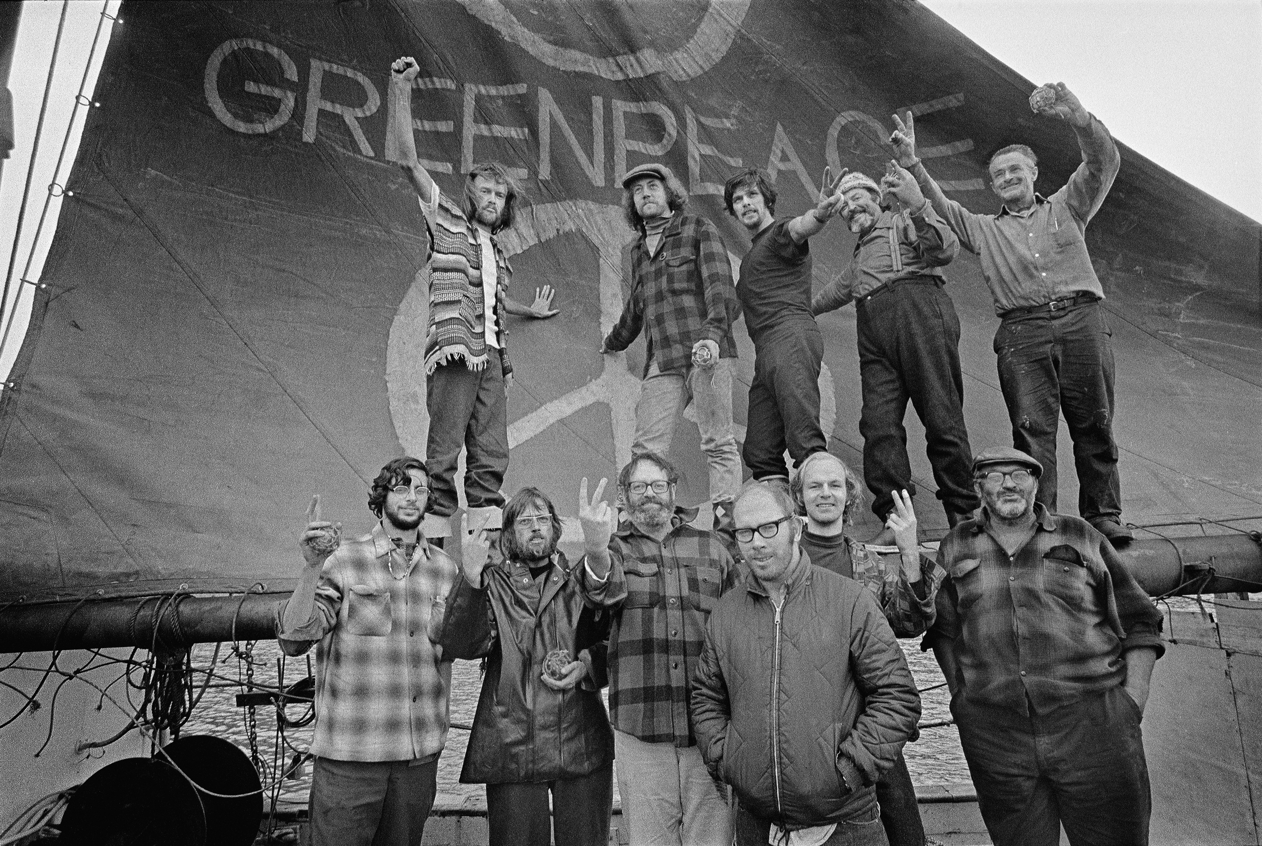 Black and white photo in which 11 people pose in front of a ship with a sail reading Greenpeace in the background.