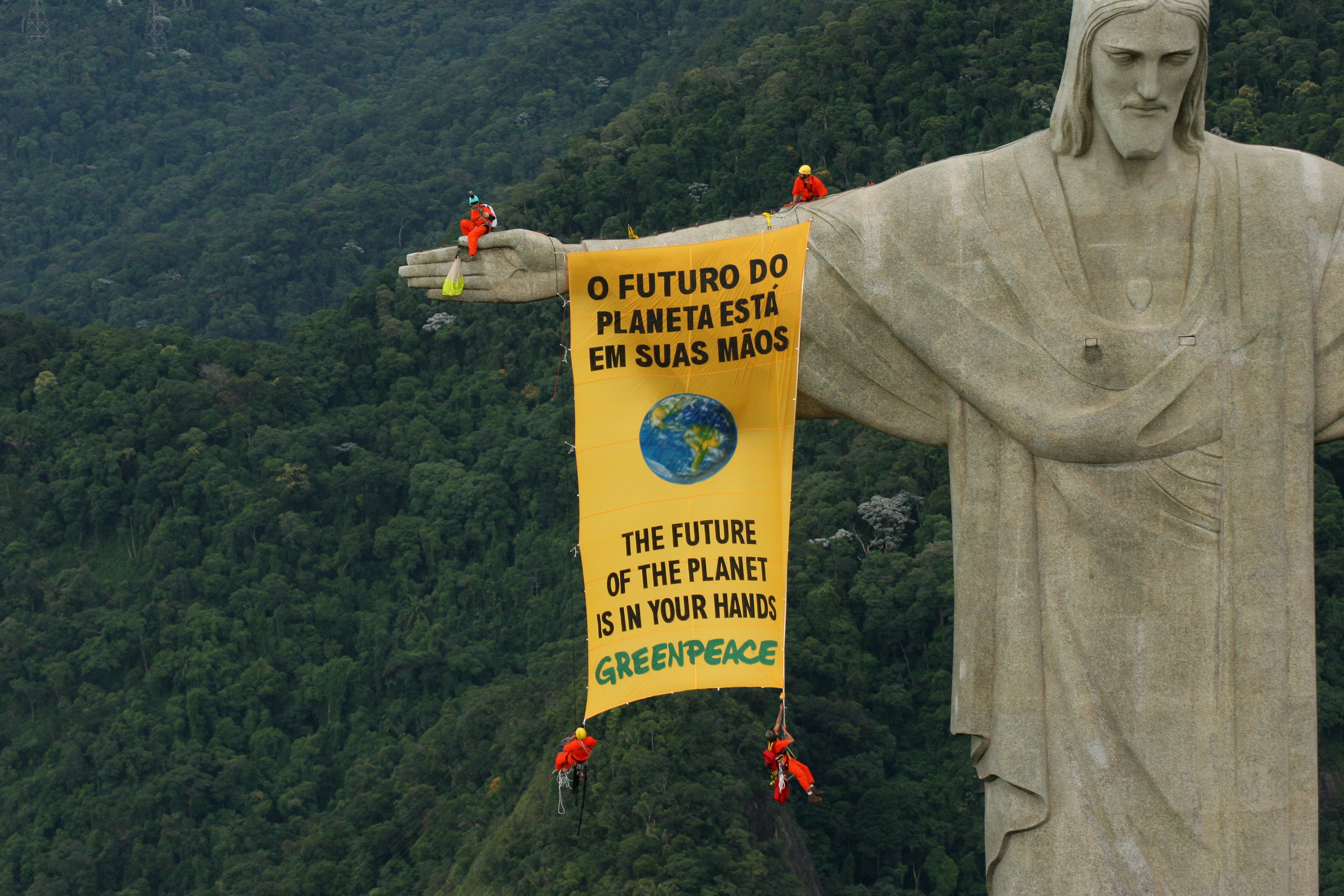 a long thin yellow banner hanging off Christ the Redeemer statue in Brazil, with four activists in red at each corner. The statue is high above a green forested background