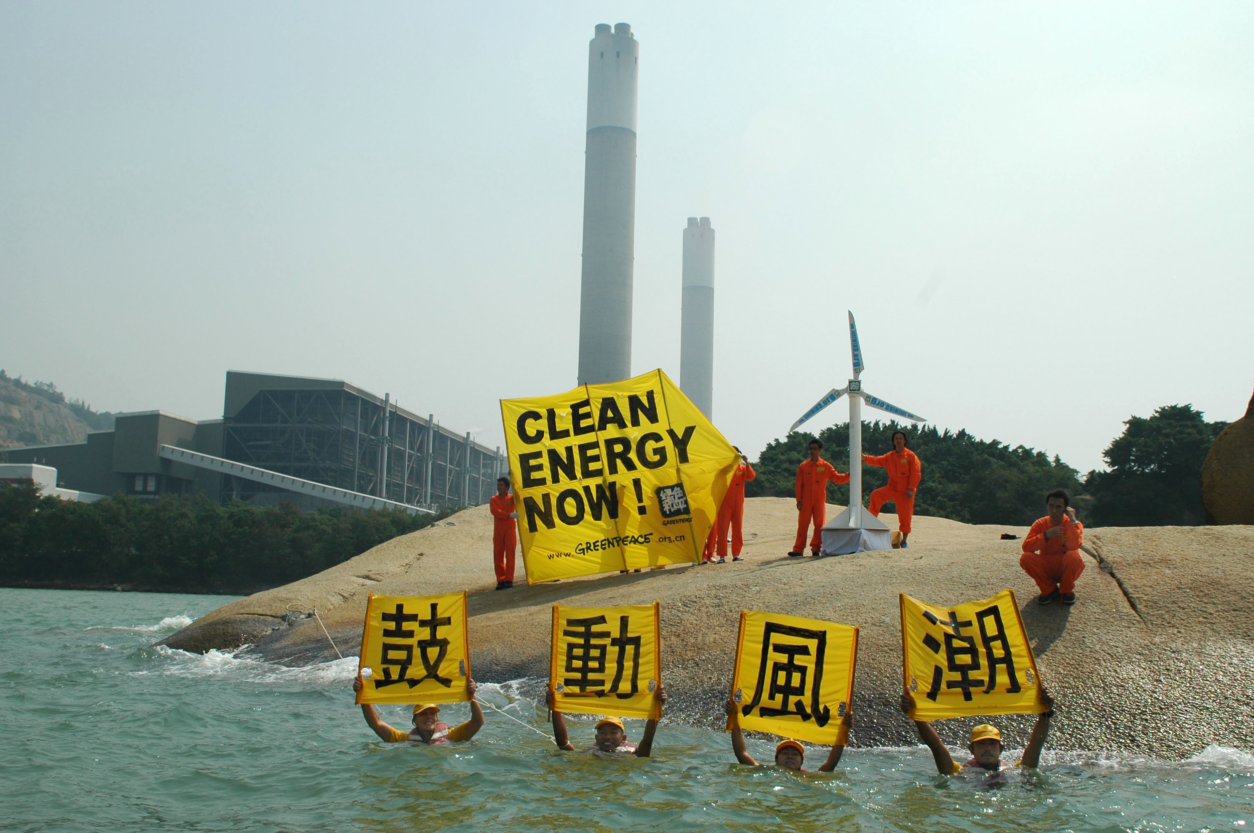 5 activists stand in front of a power station with banner reading clean energy now and a small wind turbine, there are also four activists who are in water in the foreground up to their necks with separate square Chinese character banners