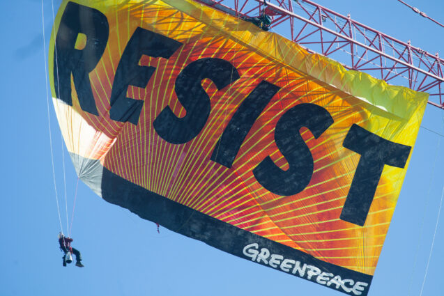 a huge orange and yellow banner filling the frame hanging from a crane reading RESIST with a person dangling off the left bottom corner