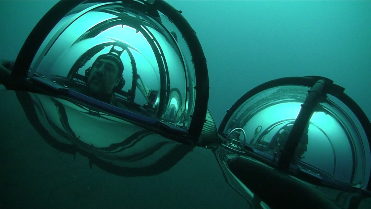 eerie underwater picture of two bubble-like vehicles with cages around them, catching the turquise green light through the clear sea