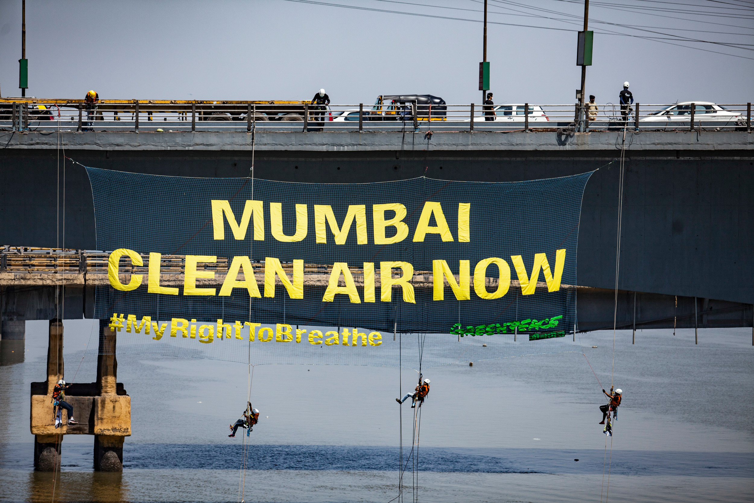 Three activists dangle on ropes off a bridge with a huge banner on it reading Mumbai Clean Air Now