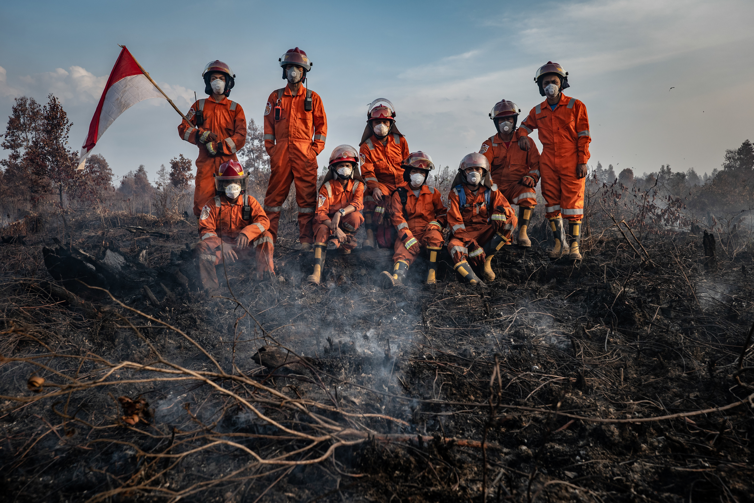nine firefighters in orange hazmat suits with masks and helmets pose for a photo on a smouldering burnt patch of land