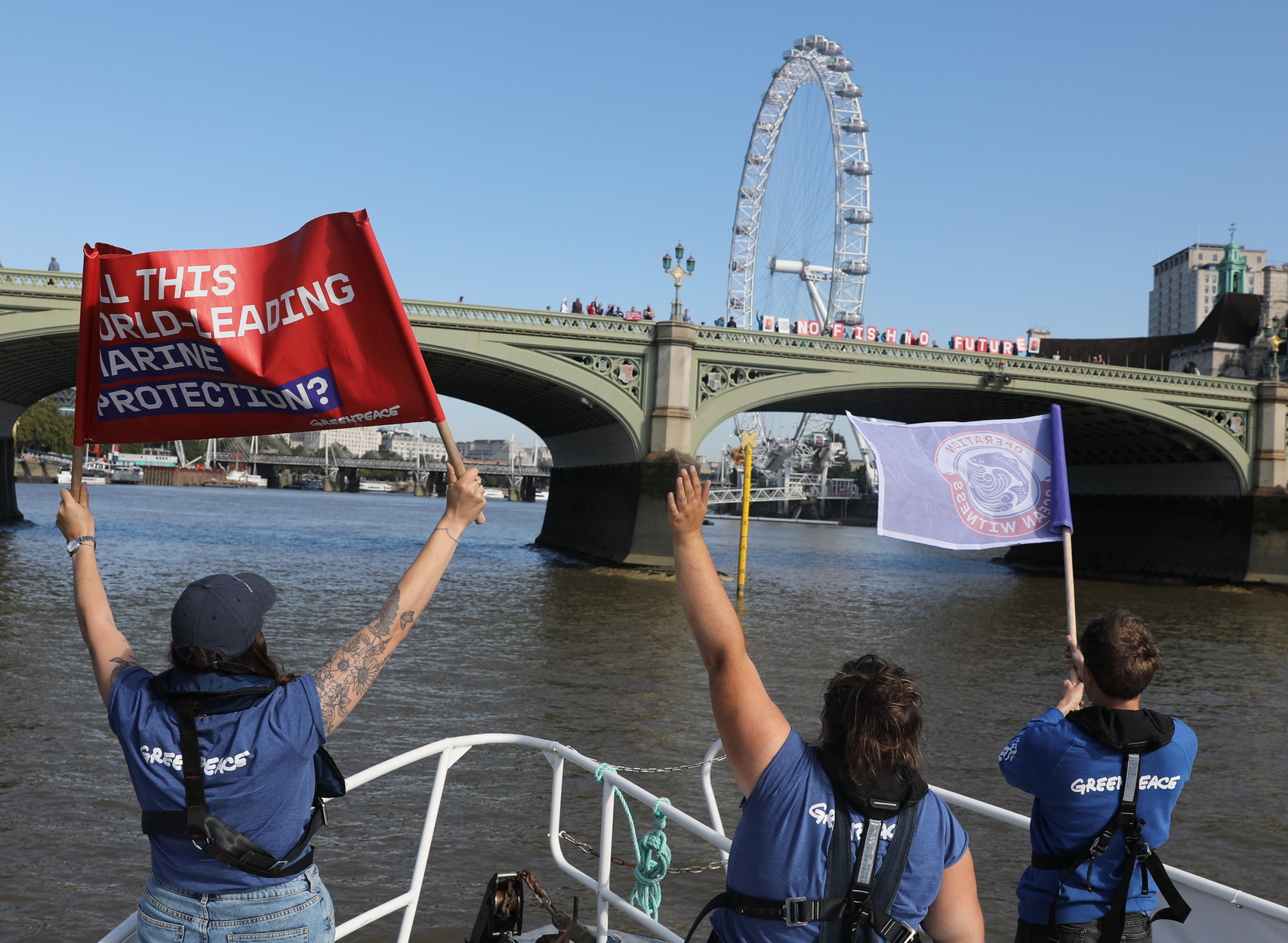 Three Greenpeace crew members wave and hold up banners towards a group of protesters on a bridge. The protesters are holding up placards reading 'No fish no future'. The 'London Eye' ferris wheel is visible in the background.