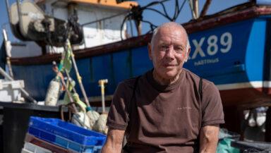 Paul Joy (brown tshirt, grey shorts, bald) sits among nets and crates on a dock. A small fishing boat is visible behind him.