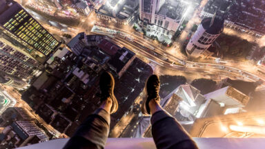 First-person view of someone sitting on the edge of a skyscraper at night. The photographer's legs and feet are seen hanging over the edge, and tall buildings and streets are visible far below.