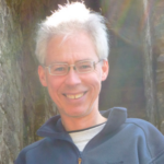 Doug Parr (white hair, glasses, zipped blue fleece) smiling into the camera
