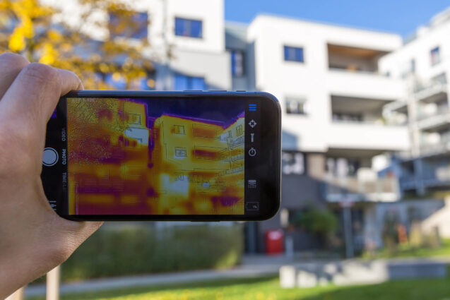 A thermal imaging camera held up to a low-rise apartment building. The camera's screen shows the temperature of different parts of the building's exterior, colour-coded in yellow, orange and purple.