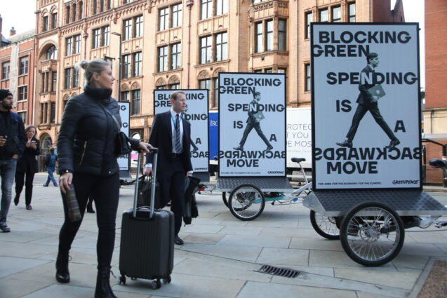 Conference delegates in business suits walk past a trio of cargo bikes with billboards mounted on the back. Each one shows a photo of Rishi Sunak photoshopped so his legs are facing backwards. Text reads 'Blocking green spending is a backwards move'.